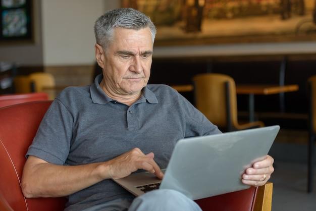 Knappe senior man met behulp van laptop en thuis binnenshuis ontspannen