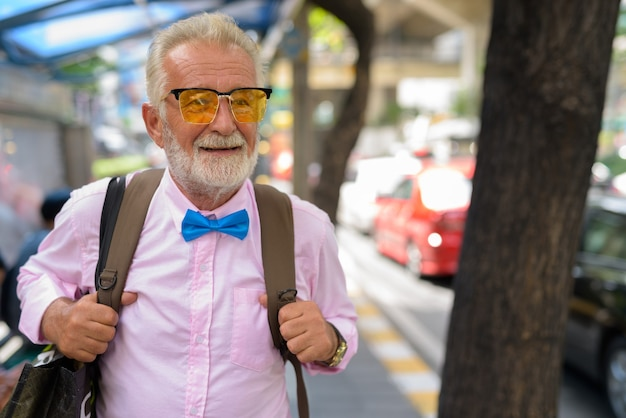 Knappe senior toeristische man verkennen van de stad bangkok, thailandia