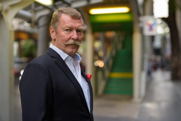 Knappe senior zakenman met snor de stad verkennen