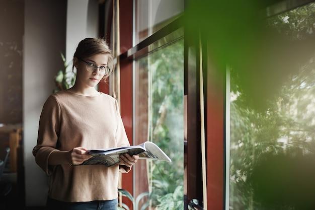 Knappe serieuze europese vrouwelijke collega in trendy en gezellige pullover, tijdschrift vasthoudend en starend met dromerige uitdrukking