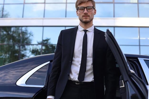 Knappe serieuze jonge zakenman die in de buurt van zijn comfortabele nieuwe auto staat en naar kantoor gaat.