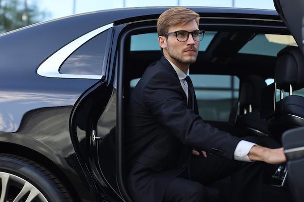 Knappe serieuze jonge zakenman die in zijn comfortabele nieuwe auto zit en naar kantoor gaat.