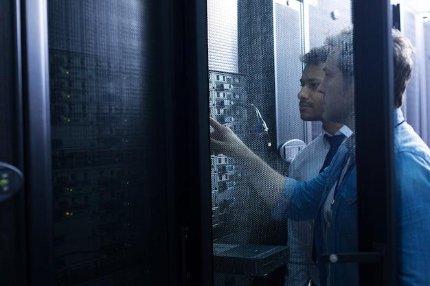 Knappe serieuze mannelijke technicus staan in de buurt van zijn collega en kijken naar de netwerkserver terwijl u op een knop drukt