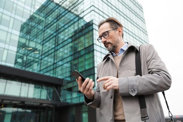 Knappe serieuze zakenman in bril die mobiele telefoon gebruikt terwijl hij in de buurt van een glazen gebouw in stedelijk gebied staat