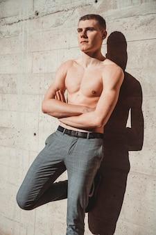 Knappe shirtless man voor een muur