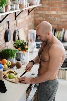 Knappe, shirtloze man in de keuken