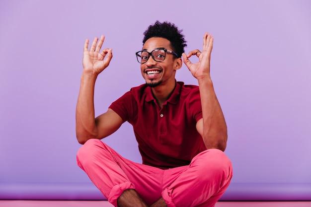 Knappe slimme kerel die grappige gezichten maakt. lachende zwarte man in goed humeur poseren in glazen.