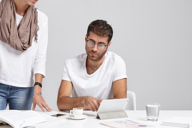Knappe slimme zakenman raadpleegt zijn collega over rapport