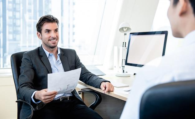 Knappe spaanse zakenman als een baas interviewen collega op kantoor