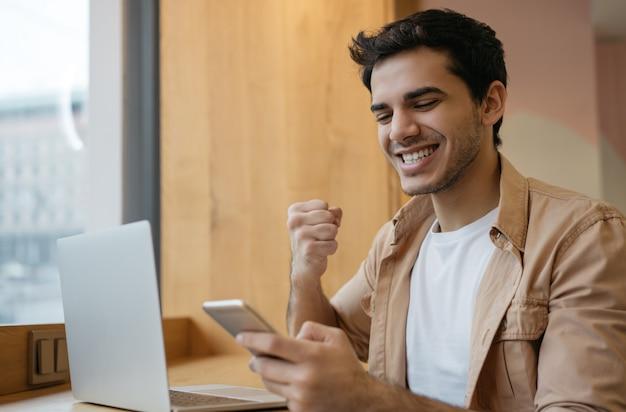 Knappe spaanse zakenman die smartphone, laptop gebruiken, die goed nieuws, vieringssucces lezen