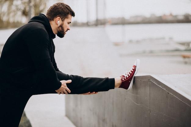 Knappe sportieve man die zich uitstrekt in park aan de rivier