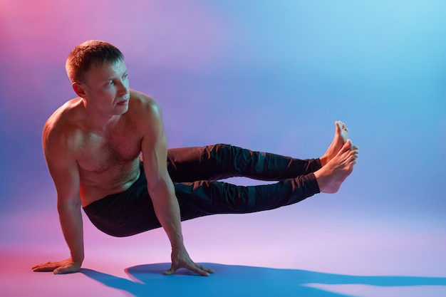 Knappe sportieve man doet yoga oefeningen tegen neon muur, staande op zijn handen en benen opzij spreiden