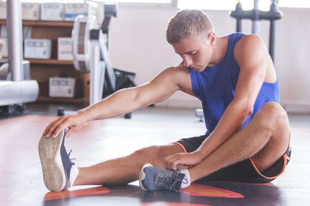 Knappe sportieve man zijn voeten strekken op de sportschool