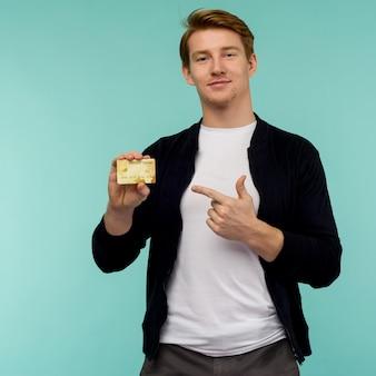 Knappe sportieve roodharige man wijzende vinger gouden creditcard op een blauwe achtergrond.