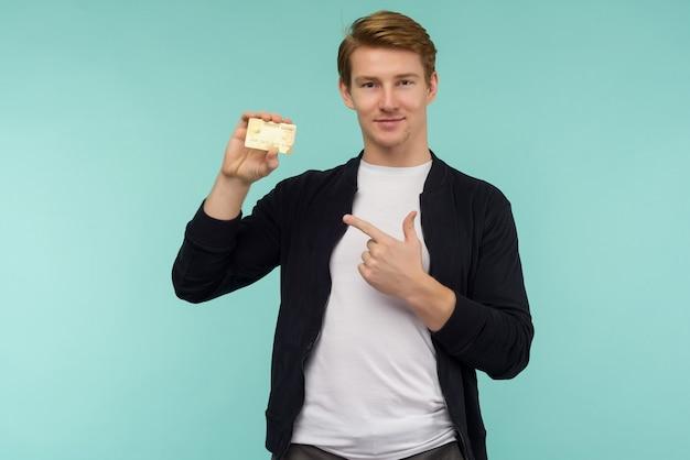 Knappe sportieve roodharige man wijzende vinger gouden creditcard op een blauwe achtergrond