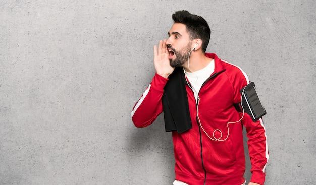 Knappe sportman die met mond wijd open aan de zij over geweven muur schreeuwt