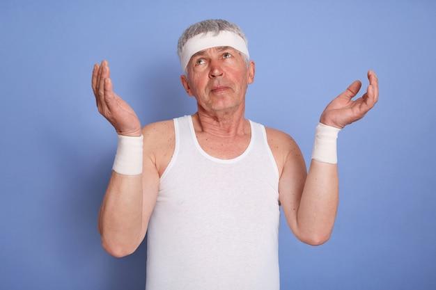 Knappe sportman van middelbare leeftijd, ziet er geen idee en verward uit, houdt de armen omhoog, heeft geen idee, draagt een wit mouwloos t-shirt en hoort een band, staand geïsoleerd.