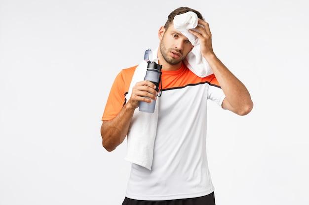 Knappe sportman veegt zweet van voorhoofd met handdoek op nek,
