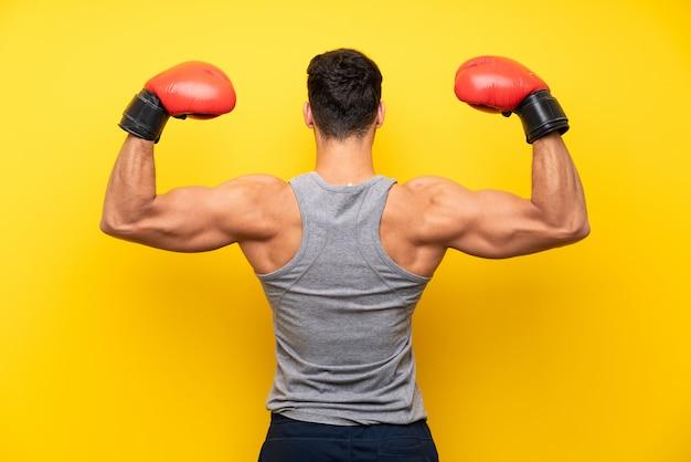 Knappe sportmens over geïsoleerde achtergrond met bokshandschoenen