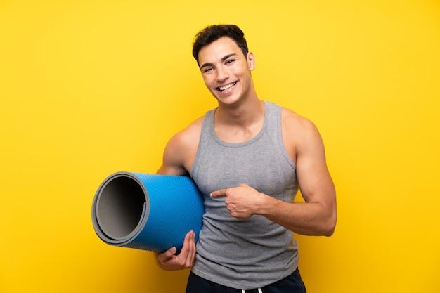 Knappe sportmens over geïsoleerde muur met mat