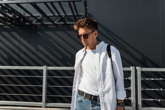 Knappe stedelijke jongeman in stijlvolle witte kleren in spijkerbroek in donkere zonnebril in een zwarte tas staat in de buurt van een modern gebouw in de stad. moderne trendy kerel buiten op een zonnige dag.