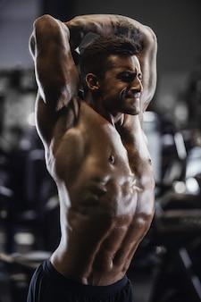 Knappe sterke atletische man oppompen spieren training fitness en bodybuilding concept achtergrond - gespierde bodybuilder fitness mannen doen armen abs terug oefeningen in de naakte torso sportschool