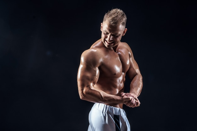 Knappe sterke bodybuilder poseren in studio op zwart