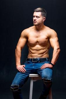 Knappe sterke kerel man zonder shirt tegen een donkere achtergrond. zittend op stoel. studiofoto. mannelijk schoonheidsconcept. detailopname.