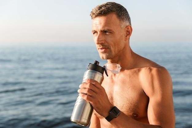Knappe sterke volwassen sportman drinken op het strand.