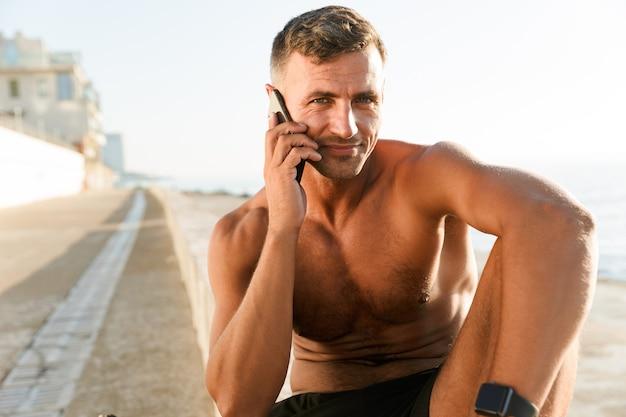 Knappe sterke volwassen sportman praten via de mobiele telefoon