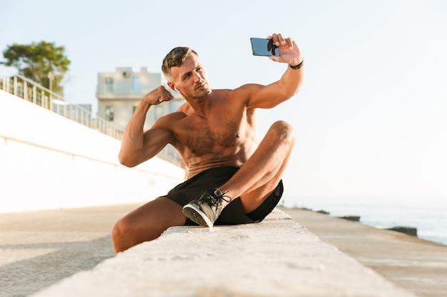 Knappe sterke volwassen sportman selfie te nemen