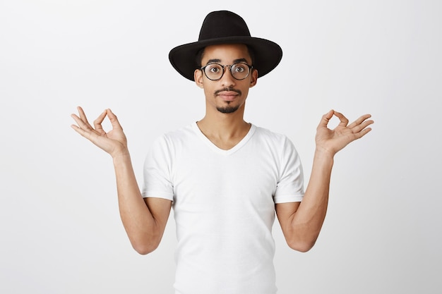 Knappe stijlvolle afro-amerikaanse man in hipster hoed en bril mediteren, doe aan yoga