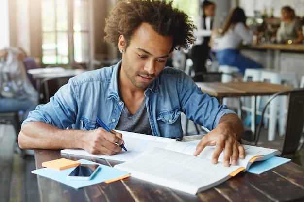 Knappe stijlvolle afro-amerikaanse universiteitsstudent studeert in café