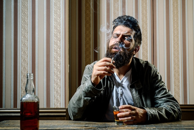 Knappe stijlvolle bebaarde man drinkt thuis na het werk. dronken man. stijlvolle man. stop met drinken. geen alcohol. roken man.