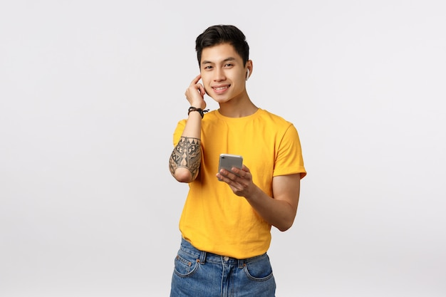 Knappe stijlvolle chinese man met tatoeages, zet een draadloze koptelefoon op, houdt de telefoon vast en lacht tevreden, luistert muziek, geniet van een mooi oortje, staande witte muur