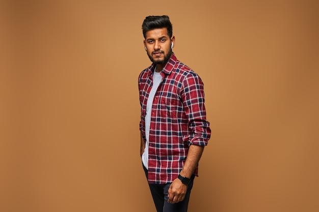 Knappe stijlvolle indiase model man in casual close poseren op pastel muur