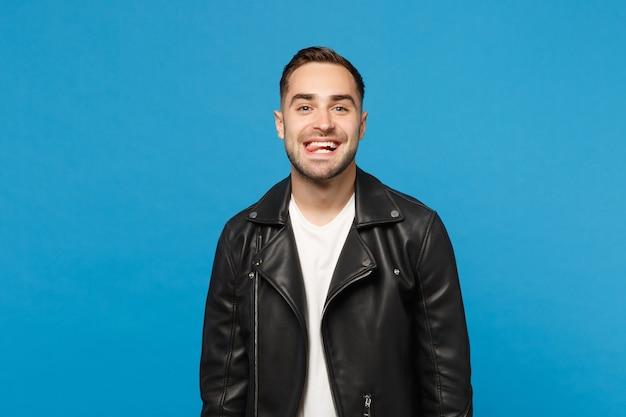Knappe stijlvolle jonge bebaarde man in zwart lederen jas wit t-shirt gek rond geïsoleerd op blauwe muur achtergrond studio portret. mensen oprechte emoties levensstijl concept. bespotten kopie ruimte.