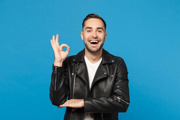 Knappe stijlvolle jonge bebaarde man in zwart lederen jas wit t-shirt op zoek camera geïsoleerd op blauwe muur achtergrond studio portret. mensen oprechte emoties levensstijl concept. bespotten kopie ruimte.