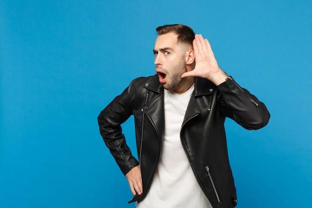 Knappe stijlvolle jonge, bebaarde man in zwart leren jas wit t-shirt probeert je te horen geïsoleerd op blauwe muur achtergrond studio portret. mensen oprechte emoties levensstijl concept. bespotten kopie ruimte