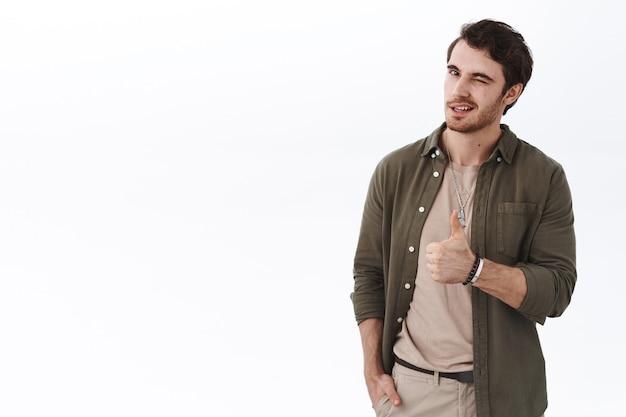 Knappe stijlvolle jonge, bebaarde man toont duim omhoog en knipoogt bemoedigend, prijst geweldig werk, zegt goed gedaan