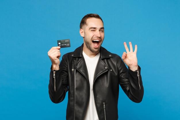 Knappe stijlvolle jonge ongeschoren man in zwart lederen jas wit t-shirt in de hand houden creditcard geïsoleerd op blauwe muur achtergrond studio portret. mensen levensstijl concept. bespotten kopie ruimte.