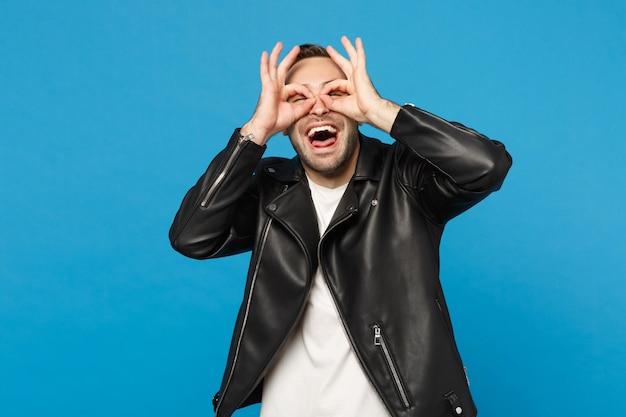 Knappe stijlvolle jonge ongeschoren man in zwart lederen jas wit t-shirt op zoek camera geïsoleerd op blauwe muur achtergrond studio portret. mensen oprechte emoties levensstijl concept. bespotten kopie ruimte