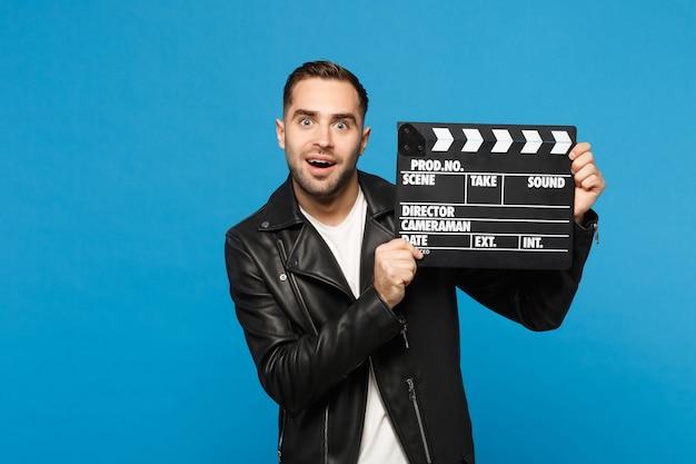Knappe stijlvolle jonge ongeschoren man in zwarte jas wit t-shirt in de hand houden film filmklapper geïsoleerd op blauwe muur achtergrond studio portret. mensen levensstijl concept. bespotten kopie ruimte.