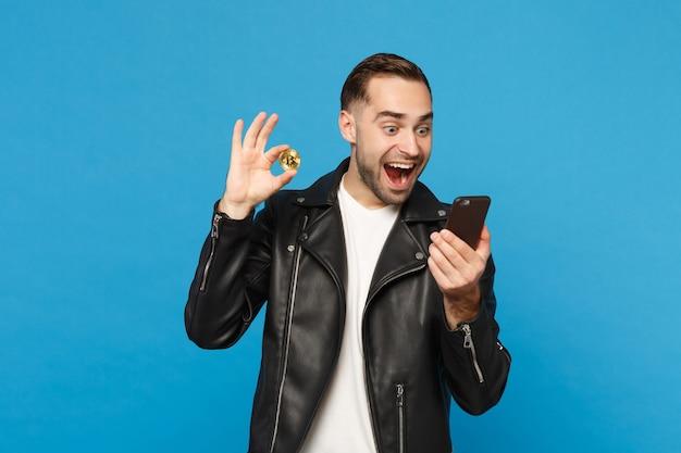 Knappe stijlvolle jonge ongeschoren man in zwarte jas wit t-shirt in de hand houden mobiel bitcoin valuta geïsoleerd op blauwe muur achtergrond studio portret. mensen levensstijl concept. bespotten kopie ruimte