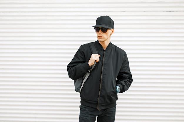 Knappe stijlvolle jongeman in zwarte mode kleding met rugzak op een witte metalen achtergrond