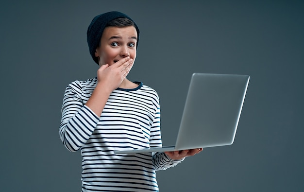 Knappe stijlvolle jongen in een gestreepte trui en hoed met een laptop in de hand bedekte zijn mond met zijn hand in verbazing geïsoleerd op grijs.