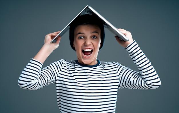 Knappe stijlvolle jongen in een gestreepte trui en hoed zette een laptop op zijn hoofd vreugdevolle verrast schreeuwen geïsoleerd op een grijze.
