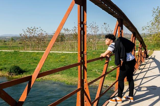 Knappe stijlvolle man die op de brug over de prachtige rivier