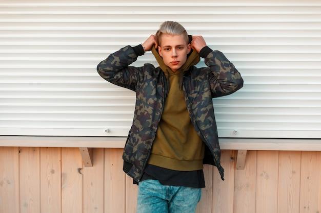 Knappe stijlvolle man in een militair jasje en zet de kap in de buurt van witte metalen muren