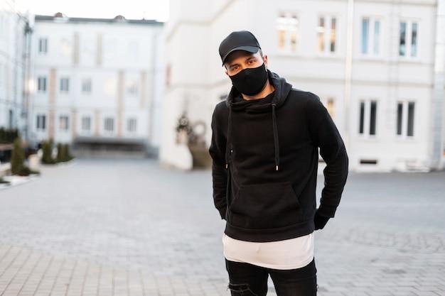Knappe stijlvolle man met een beschermend masker en een zwarte pet in een modieuze zwarte hoodie in de stad. stedelijke herenkledingstijl en pandemie
